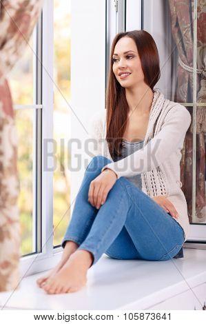 Beautiful young lady on the windowsill.