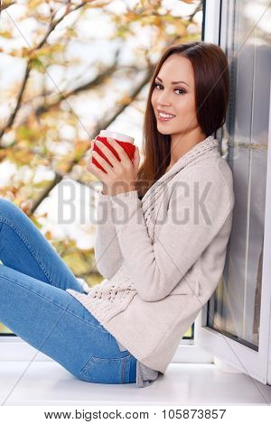 Woman on the windowsill with a cup of drink.