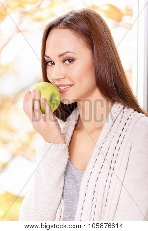 Young smiling girl is about to eat apple.