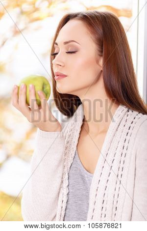 Woman with closed eyes enjoys the smell of apple.