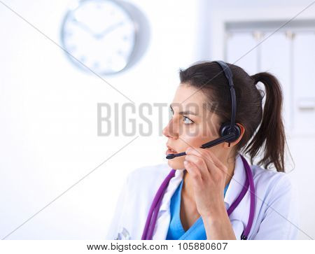 Doctor wearing headset sitting behind a desk with laptop