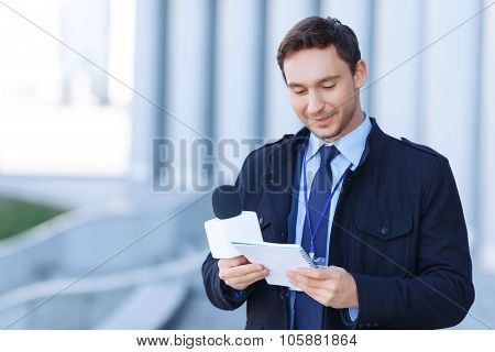 Journalist is reading his current strategy written in notepad.