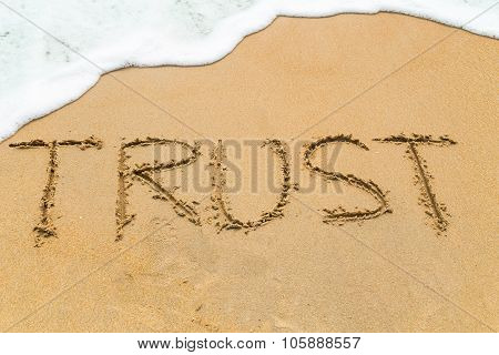 TRUST inscription written on sandy beach with wave approaching. poster