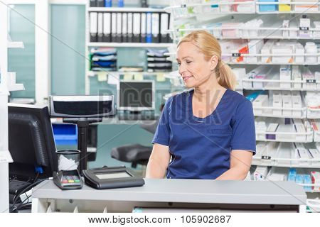 Female assistant looking at computer while sitting at cash counter in pharmacy