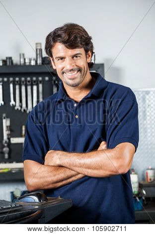 Portrait of happy male mechanic standing arms crossed in auto repair shop