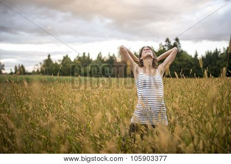 Young Woman Standing In The Middle Of Autumn Meadow With High Golden Grass