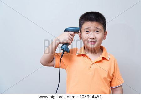 Asian boy joking doing a suicide gesture with a fake gun made with barcode scanner aim at his head on gray wall background with soft shadow poster