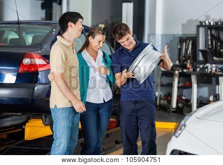 Happy male technician and couple looking at metallic hubcap in garage