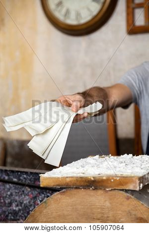 Cropped image of worker giving paper strips in factory poster