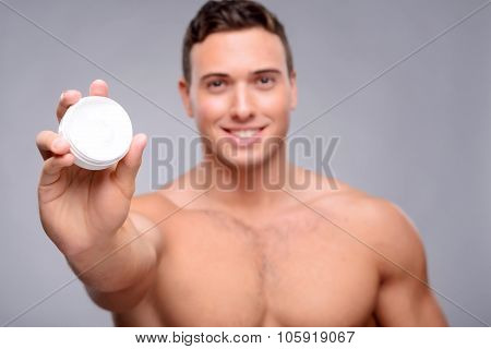 Pleasant man using cream