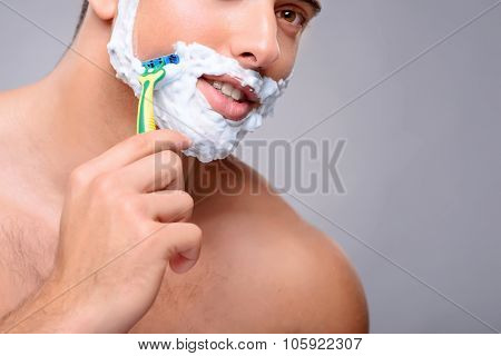 Be healthy. Close up of pleasant handsome guy holding shaver and shaving while taking care of himself poster