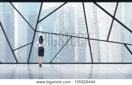 Rear View Of A Full Length Lady In Formal Clothes Who Is Looking Out The Window In A Modern Panorami