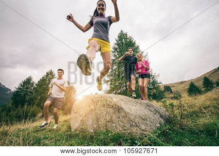 Runners training on a off road track - Group of hikers walking in the nature at sunset - Friends taking an excursionon a mountain poster