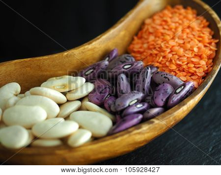 Beans and Red lentils in a bean shaped wooden bowl