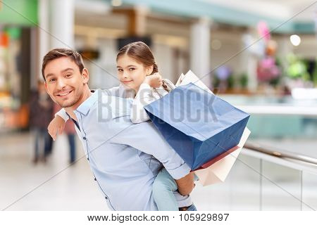 Father and daughter having fun in shopping mall