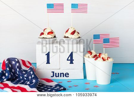 Greeting card on the day of the flag of America two cupcakes two desserts with cream strawberries and American flags perpetual calendar with the words June 14 on a white and blue background