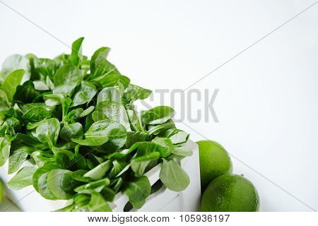 Watercress Salad In White Wooden Box With Limes Around Close Up