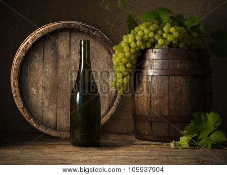 Glass white wine and bunch grapes on background of wooden