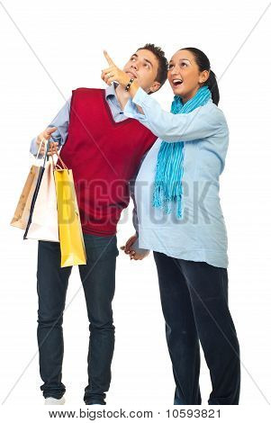 Pregnant Couple At Shopping Pointing Up