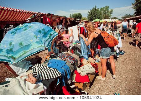 Woman Watching Second Hand Shirts In A Outdoor Market