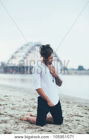 Sad Man Kneeling On The Sand By The River