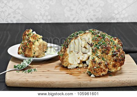 One Whole Roasted Cauliflower Head With A Slice Removed.