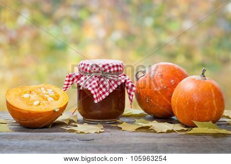 Jar of pumpkin jam puree or sauce and small ripe pumpkins on wooden table. Autumn still life. Selective focus. poster
