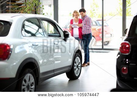 couple  in car showroom reading brochure and choosing new car