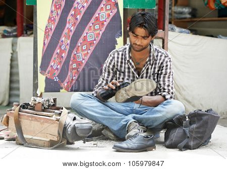 young shoeblack man cleaning boots on street in india poster