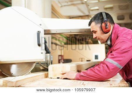 process of carpenter worker with circular saw machine at wood beam cross cutting during furniture manufacture