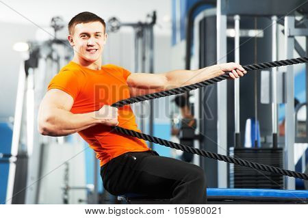 athlete bodybuilder man doing back muscles exercises at weight machine in fitness sport club gym