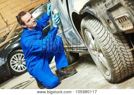 auto mechanic worker sanding car body at automobile repair and renew service station shop by sandpaper