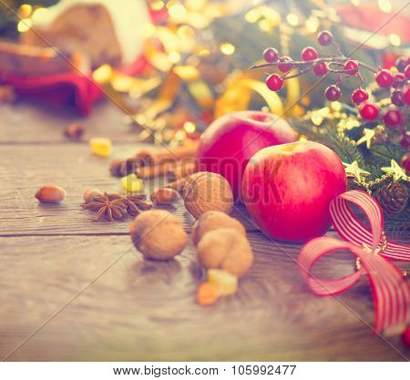 Christmas holiday table setting, decorated with garlands, baubles, walnuts, hazelnuts, cinnamon sticks. Warm colors toned. Traditional Xmas sweets food. Vintage style toned image. x-mass