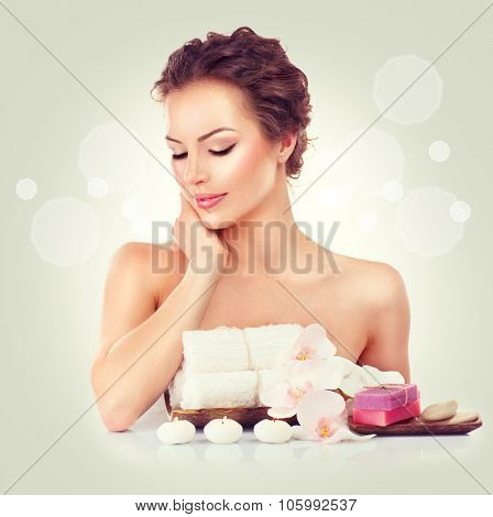Beauty Spa Woman touching her soft skin, Beautiful girl portrait. Day spa, wellbeing concept. Handmade soap bars, towels, candles and orchid flowers on her table
