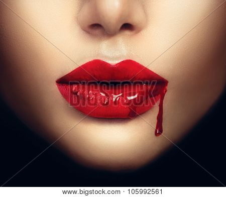 Sexy Vampire Woman lips with dripping blood. Fashion Glamour Halloween art design. Closeup of glamourous girl vampire mouth