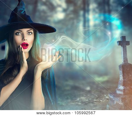Halloween Witch with a magic in a dark Old Spooky cemetery. Beautiful young woman in witches hat and costume holding magical light in her hand. Halloween art design