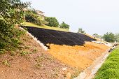 Slope erosion control with grids and earth on steep slope. poster
