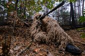 Sniper in camouflage in forest with a rifle aiming at enemy poster