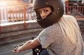Female biker girl with black full face motorcycle helmet. Young Blonde woman in leather jacket sitting on vintage custom motorbike. Outdoors lifestyle portrait poster