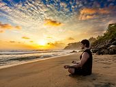 Young sporty fit man doing yoga meditating in padmasana lotus pose on tropical beach on sunset poster
