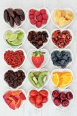 Fresh mixed fruit background selection with fruits high in antioxidants, vitamin c and dietary fibre in heart shaped dishes. poster