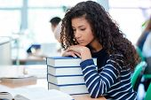 Young curly african american girl is sitting in a sad mood putting her head on books poster