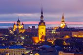 Aerial cityscape with Medieval Old Town illuminated in evening twilight and City Hall, St. Olaf Baptist Church and Alexander Nevsky Cathedral in Tallinn, Estonia poster