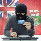 Dark-skinned hacker holding credit card with Canadian province flag on background - Manitoba poster