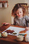 cute child girl making herbarium at home, autumn seasonal crafts poster
