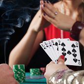 Poker game with drinks and cigarettes in casino poster