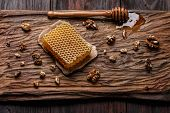 Honey dip honeycomb and walnuts on carved wooden serving plate over burnished wood table poster
