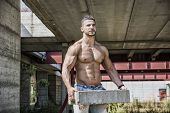 Sexy construction worker shirtless showing muscular body, holding big bricks poster