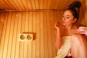 Spa beauty treatment and relaxation concept. Woman relaxing in wooden sauna room having fun blowing soap bubbles poster