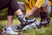 Happy couple putting on roller blades in the countryside poster